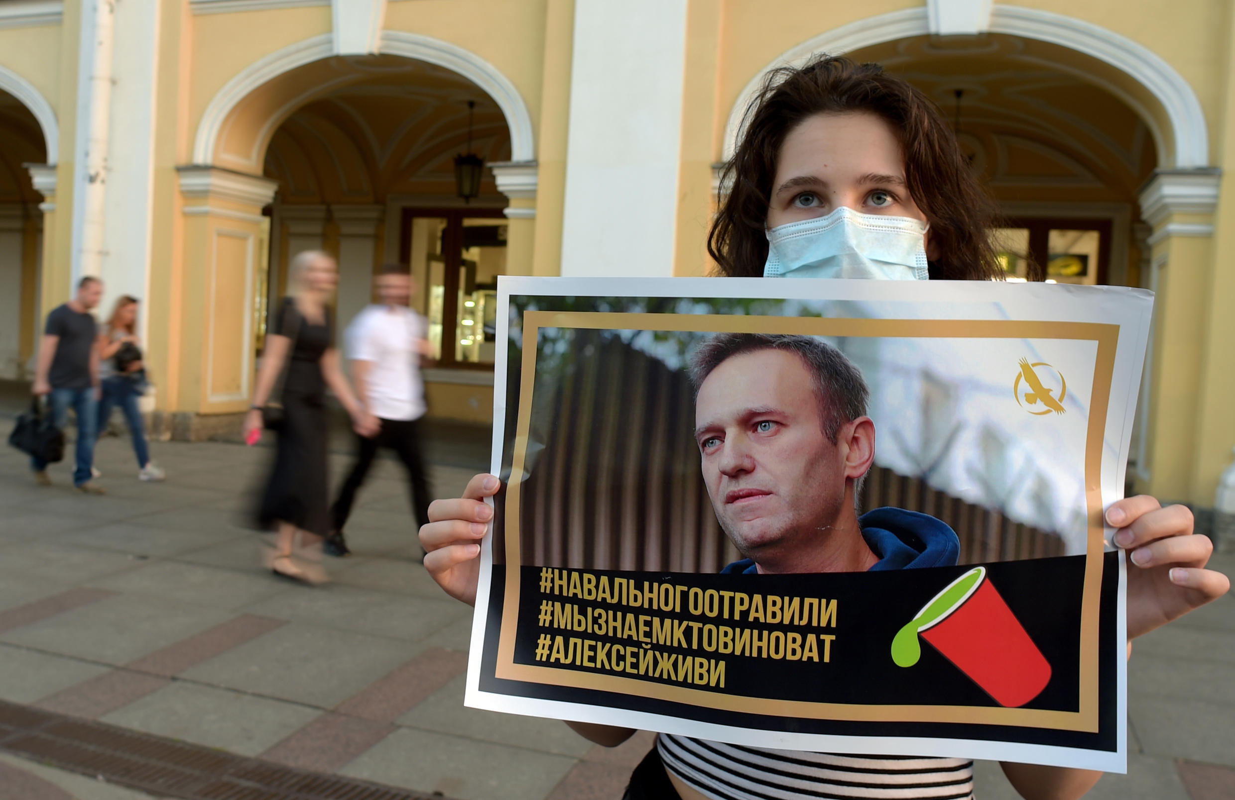 A supporter of Alexei Navalny holds up a picture of the Kremlin opponent after he was taken ill with suspected poisoning