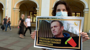 A supporter of Alexei Navalny holds up a picture of the Kremlin opponent after he was taken ill with poisoning