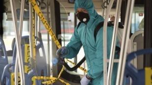 Un trabajador municipal desinfecta un trolebús en una estación en el norte de Quito, el 3 de junio de 2020, cuando Ecuador comienza a reabrir su economía en medio de la nueva pandemia de coronavirus del COVID-19.