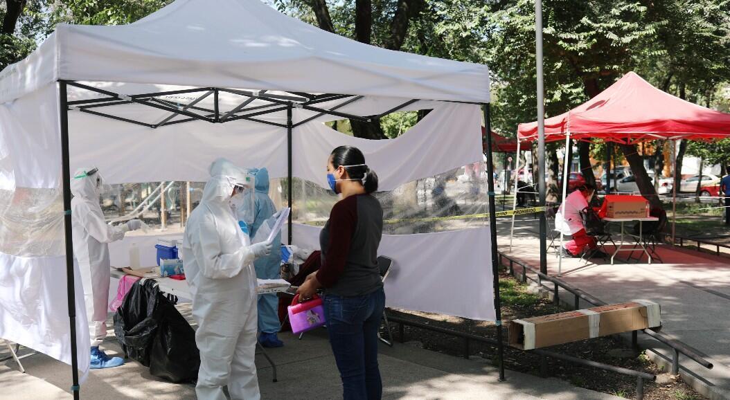 Un trabajador de salud, con equipo de protección personal, da instrucciones antes de tomar una muestra de hisopo a una mujer para la prueba Covid-19, en el Parque Lázaro Cárdenas, en Ciudad de México, México, el 24 de julio de 2020.