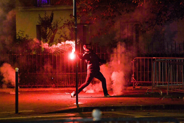 Un joven lanza una bengala a la policía el 23 de agosto de 2020, en París, Francia, luego de la derrota del PSG ante el Bayern Múnich en la final de la Champions League que se disputó en Portugal.