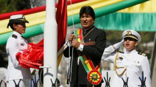 El presidente de Bolivia, Evo Morales, levanta una bandera durante una ceremonia del denominado 'Día del Mar', en La Paz, Bolivia, el 23 de marzo de 2019.