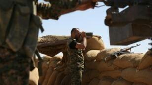 مقاتل من وحدات حماية الشعب الكردية يراقب من موقع عسكري في الحسكة