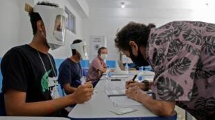 Voluntarios con mascarillas protectoras y escudos faciales esperan mientras un hombre firma antes de votar durante la segunda ronda de las elecciones municipales en el Centro Integrado de Educación Pública Ayrton Senna (CIEP) de la favela Rocinha en Río de Janeiro, Brasil, el 29 de noviembre de 2020.