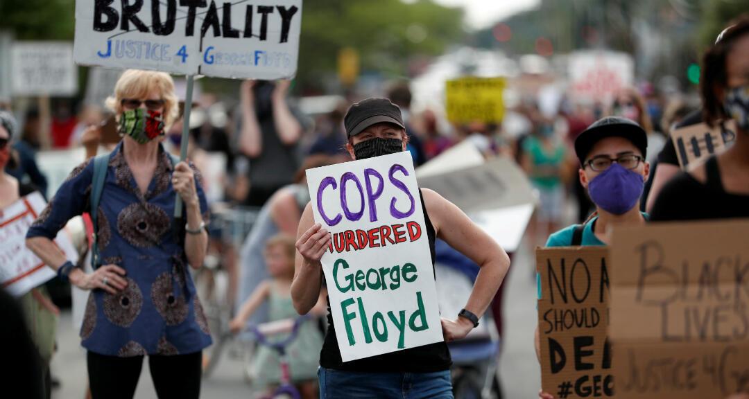 """Manifestantes se reúnen en la escena donde George Floyd murió a manos de agentes de la Policía con un cartel que dice """"Los policías asesinaron a George Floyd"""". Minneapolis, Minnesota, EE. UU. el 26 de mayo de 2020."""