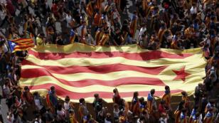 Un grupo de jóvenes carga la bandera indepedentista en Barcelona el 28 de septiembre de2017.