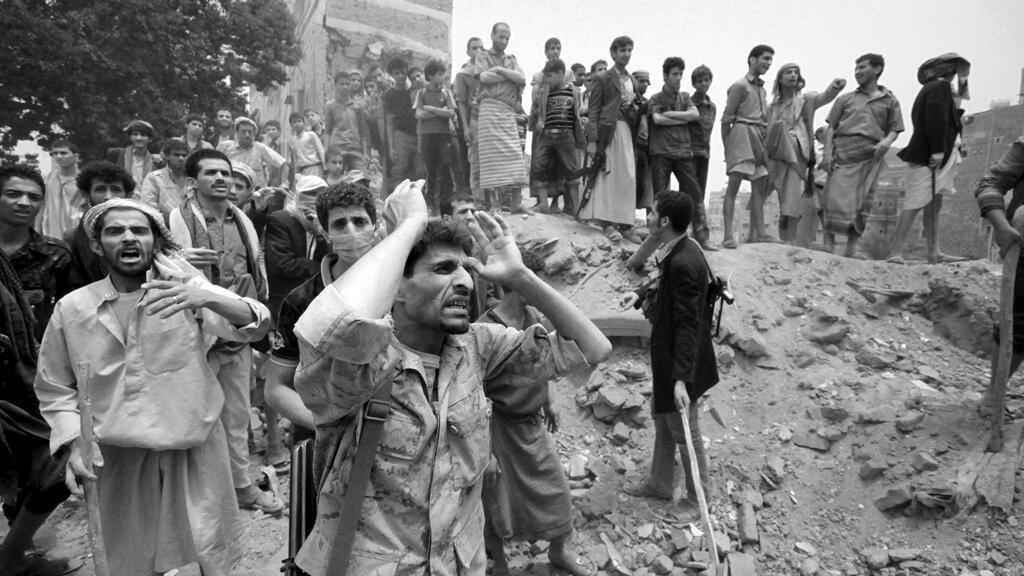 Foto de archivo de un combatiente gritando para dispersar a las personas del sitio de un ataque aéreo en Saná, capital de Yemen, el 12 de junio de 2015.