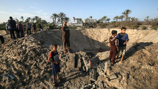Palestinian children at a crater caused by an Israeli rairstrike launched in response to rocket fire, in Khan Yunis in southern Gaza Nov. 2, 2019.