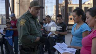 Un agent des douanes et de la protection aux frontières vérifie des documents de réfugiés à El Paso, à l afrontière avec le Mexique, le 16 mai 2019..
