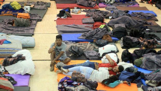 Los migrantes descansan en un centro deportivo que actualmente se usa como refugio temporal en Tijuana.