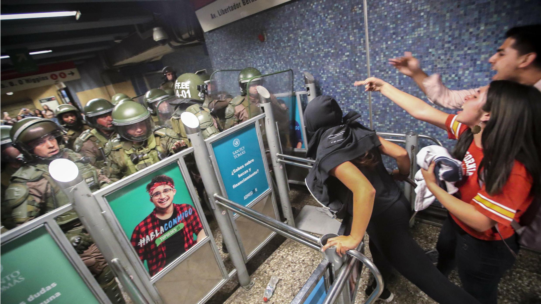 Carabineros de la Policía chilena cierran el acceso a la estación del metro Los Héroes en medio de una manifestación este viernes 18 de octubre de 2019, en Santiago, Chile.