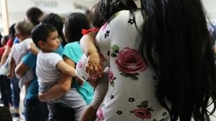 Women and their children, many fleeing poverty and violence in Honduras, Guatamala and El Salvador, arrive at a bus station following release from Customs and Border Protection in McAllen, Texas, USA on June 22, 2018.