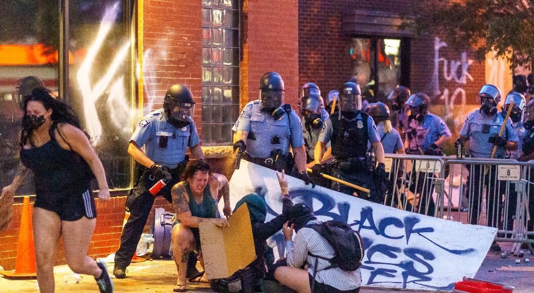 Un grupo de policías reacciona con gas pimienta contra algunos manifestantes, durante una protesta por la muerte de George Floyd, en Minneapolis, Estados Unidos, el 27 de mayo de 2020.