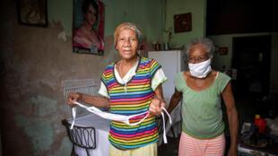 Las ancianas cubanas Olga y Carmen Moré O'Farill, de 74 y 85 años, salen hasta la puerta de su casa en La Habana, el 2 de junio de 2020.