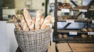 Un panier de baguettes tradition dans une boulangerie française.