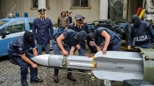 This handout picture released by the Italian police (Polizia di Stato) of Turin, on July 15, 2019, shows italian policemen carry an air-to-air missile, as part of a big cache of guns and ammunition that was seized by the Turin special police force, called Digos, led the operations, assisted by police in Milan, Varese, Forli and Novara.Anti-terrorism police in northern Italy have seized an air-to-air missile and other sophisticated weapons during raids on far-right extremist groups