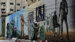 Palestinian artists paint a mural in a show of support for Palestinian prisoners held in Israeli jails amid the COVID-19 pandemic, in Gaza City on April 20