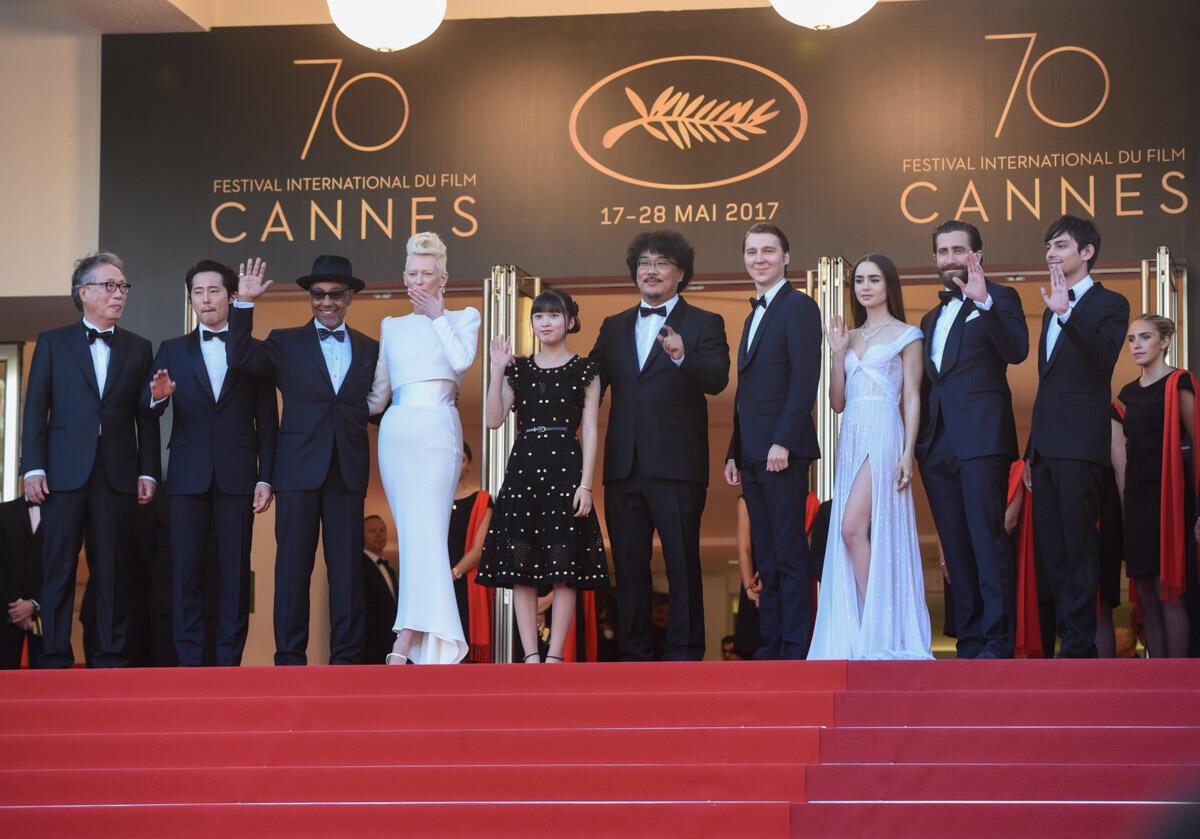 """L'équipe du film """"Okja"""" pose au sommet des marches autour du réalisateur sud-coréen Bong Joon-ho. Le long-métrage a reçu un accueil très favorable de la critique malgré la polémique autour de son producteur, Netflix."""