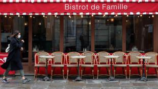 Una mujer con una mascarilla protectora pasa por un restaurante en París, el 5 de octubre de 2020.
