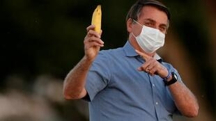 FILE PHOTO: Brazil's President Jair Bolsonaro holds a banana before a ceremony of lowering the national flag for the night, amid the coronavirus disease (COVID-19) outbreak, at the Alvorada Palace in Brasilia, Brazil, July 24, 2020.