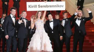 El equipo de 'Leto' llega a la proyección de la cinta con una pancarta con el nombre de su director, el ruso Kirill Serebrennikov, quien no pudo asistir por estar en arresto domiciliario en Moscú, el 9 de mayo de 2018.