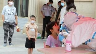 Un trabajador sanitario con indumentaria protectora toma una muestra de saliva a un niño para hacer una prueba del coronavirus, el 27 de julio de 2020 en Dalian, al noreste de China