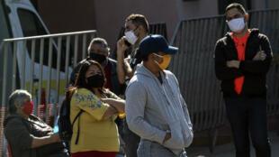 Gente hace cola frente a un hospital esperando su turno para hacerse una prueba de coronavirus COVID-19, en Santiago, el 18 de mayo de 2020, en medio de la nueva pandemia.