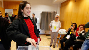 Laura Sancho, de 18 años, votando por primera vez en su vida, emite el voto por poder del ex presidente de Cataluña, Carles Puigdemont, en una mesa electoral en Sant Cugat del Valles, España, el 21 de diciembre de 2017.