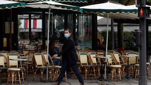 A woman wearing a protective face mask walks past Les Deux Magots cafe in Paris on October 5, 2020.