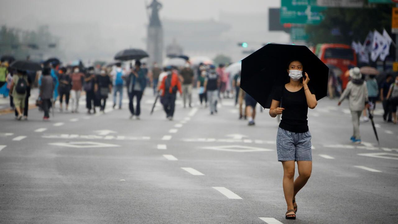 Una mujer con una máscara pasa junto a miembros de grupos cívicos conservadores que participan en una protesta contra el Gobierno, mientras aumentan las preocupaciones por una nueva ola de casos de coronavirus. Seúl, Corea del Sur, el 15 de agosto. 2020.