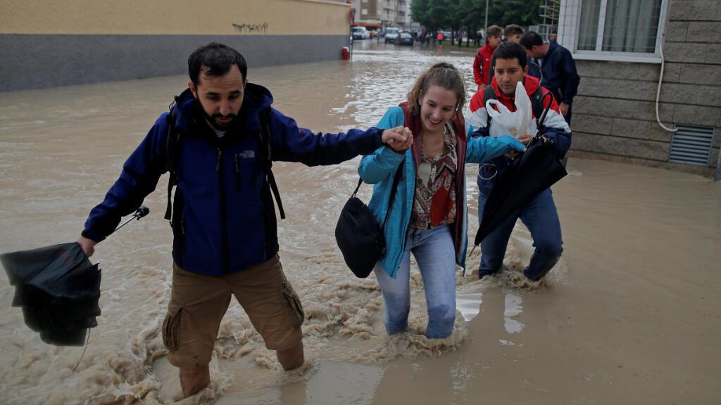 La gente vadea por una calle inundada cerca del desbordante río Segura, mientras las lluvias torrenciales azotan Orihuela, cerca de Murcia, España.