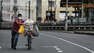 Un hombre camina junto a su bicicleta cargada de víveres por una vacía calle en Quito, Ecuador el 3 de mayo de 2020.