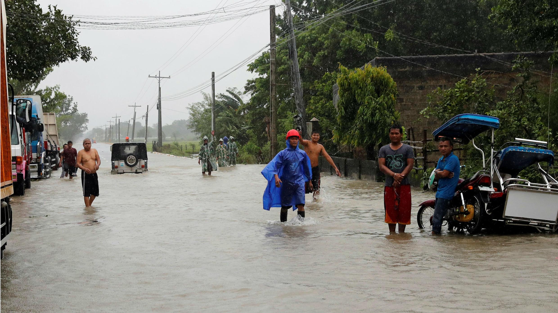 Varias personas bloqueadas en una carretera parcialmente inundada, después de que el tifón Mangkhut golpeara la isla principal de Luzón. 15 de septiembre de 2018.