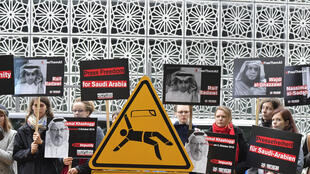 Reporters without Borders members hold signs depicting arrested Saudi writer, dissident and activist, Raif Badawi, assasinated Saudi journalist Jamal Khashoggi and arrested Saudi journalist Wajdi al-Ghazzawi outside the Saudi Arabian Embassy to Germany in Berlin on October 1, 2019.