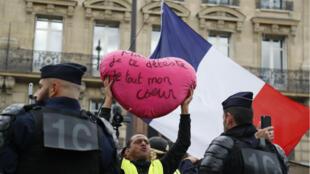 Un Gilet Jaune brandit une pancarte adressée au président Macron à Paris, le 28 septembre 2019.