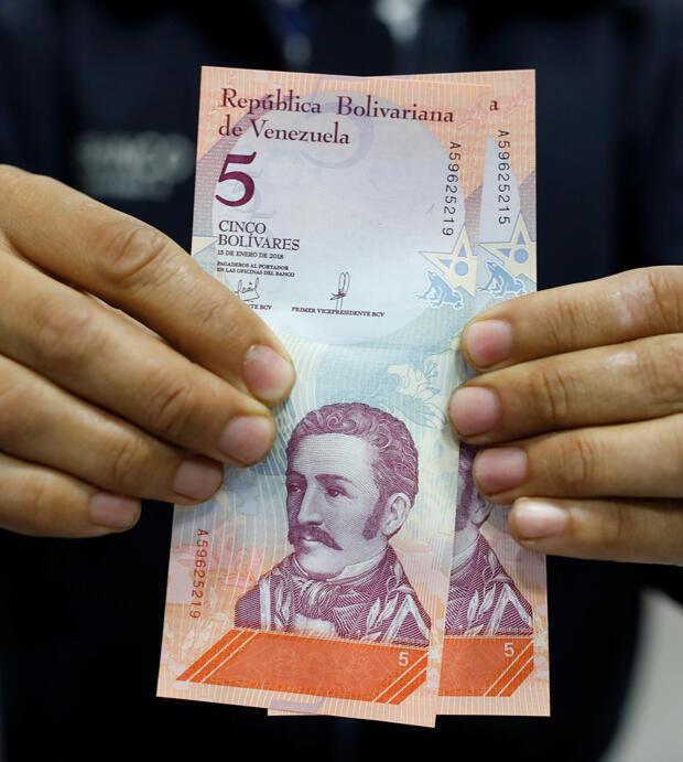 Un hombre muestra los nuevos billetes de bolívar soberano, después de que los retirara de un cajero automático en una sucursal del banco Mercantil en Caracas, Venezuela, el 20 de agosto de 2018.