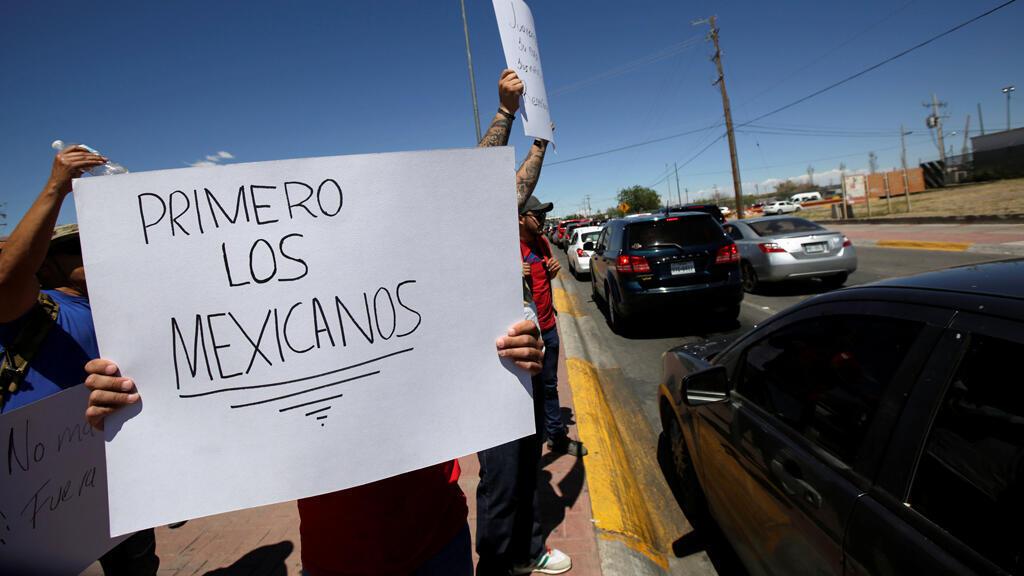 """Un manifestante sostiene un cartel que dice """"Primero los mexicanos"""" mientras protesta con otros contra el flujo de migrantes de América Central en el puente fronterizo de Córdoba- América en Ciudad Juárez, México, el 7 de abril de 2019."""