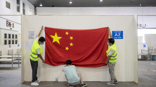 Workers remove a Chinese flag in July 2020 as they demolish installations in Wuhan, where the virus first emerged