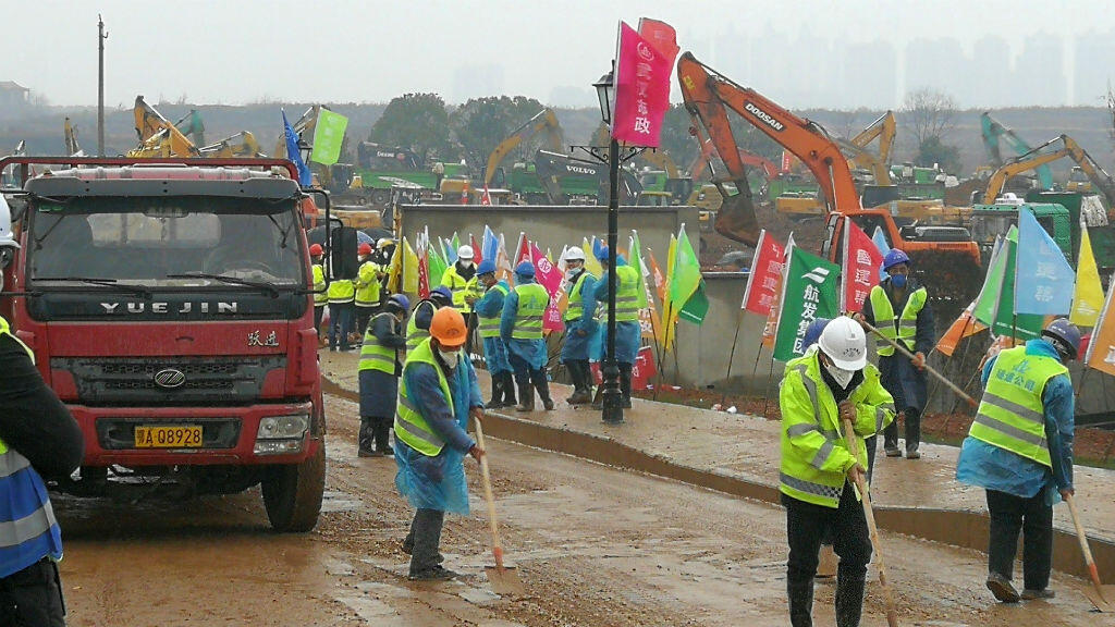 Decenas de trabajadores construyen un hospital para tratar a los pacientes de un nuevo coronavirus en las afueras de Wuhan, China, el 24 de enero de 2020.