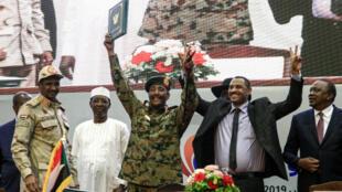 Ahmed Al-Rabie, représentant de l'Alliance pour la liberté et le changement (deuxième à partir de la droite), fait le signe de la victoire en compagnie du général Abdel Fattah al-Burhan(au centre), chef du Conseil militaire, après avoir signé l'accord de transition vers un pouvoir civil, à Khartoum, le 17août2019.
