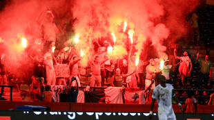 Les supporters algériens allument des fumigènes pour exprimer leur colère en fin de match face à la prestation médiocre des Fennecs.