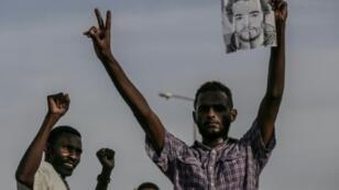 متظاهر سوداني يحمل صورة زميله الذي قتل في فض دام لاعتصام أمام مقر قيادة الجيش في العاصمة الشهر الفائت، في مسيرة لتأبين الضحايا في الخرطوم في 13 تموز/يوليو 2019.