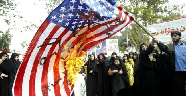 متظاهرون إيرانيون يحرقون العلم الأمريكي.