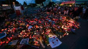 Des personnes rendent hommage aux victimes de la fusillade de Munich, dimanche 24 juillet 2016, devant le centre commercial où a eu lieu la tuerie.