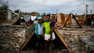 Iris Daniel, 57, Lovely Saint-Pierre, 32, and Evanston Daniel, 5, pose on May 25, 2019, outside a makeshift shelter on the site of their home which was burned during a November 2018 gang war in Port-au-Prince