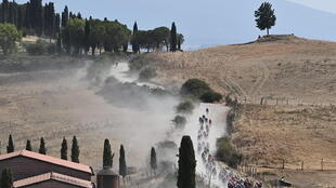 The pack of riders pedal through a dusty gravel road during the one-day classic cycling race Strade Bianche (White Roads) on August 1, 2020 around Siena, Tuscany.