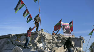 Palestinians place a portrait of alleged Palestinian assailant Qassam Barghouti atop the rubble of his second-floor family apartment after it was partially demolished by Israeli forces in the village of Kobar in the occupied West Bank