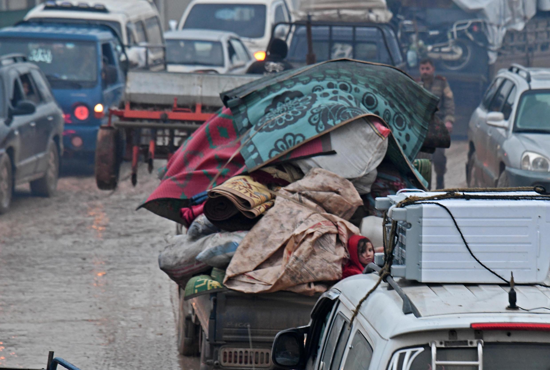Sirios desplazados del sur de la provincia de Idlib viajan en vehículos cargados de muebles, cerca de la frontera con Turquia.