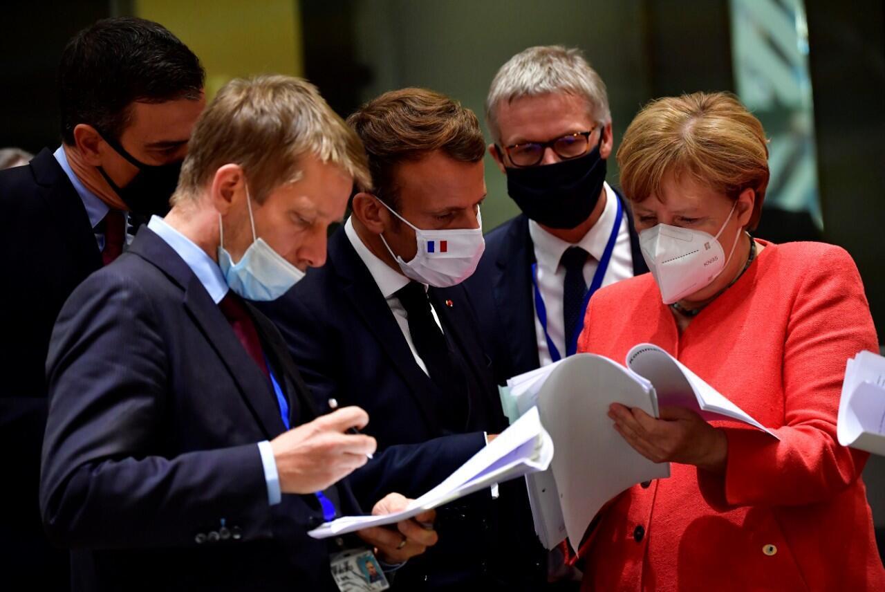 El presidente de Francia, Emmanuel Macron (cen.) y la canciller de Alemania, Angela Merkel, examinan documentos junto a otros líderes europeos durante la cumbre de la UE en Bruselas, Bélgica. 20 de julio de 2020.