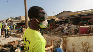 A member of local hygiene services wears a face mask during the street cleaning operation and demolishing of informal shops to stop the spread of coronavirus disease (COVID-19) in Dakar, Senegal March 22, 2020.